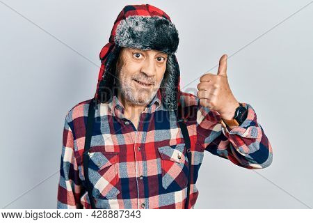 Handsome mature man wearing winter hat with ear flaps smiling happy and positive, thumb up doing excellent and approval sign