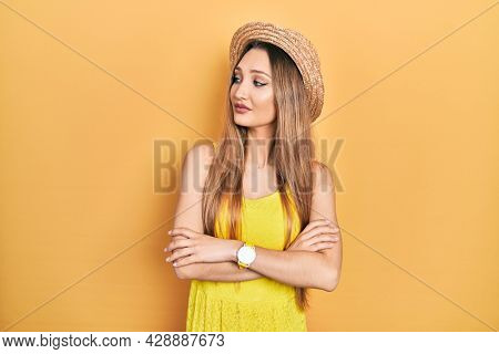 Young blonde girl wearing summer hat looking to the side with arms crossed convinced and confident