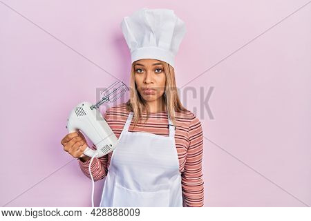 Beautiful hispanic woman holding pastry blender electric mixer depressed and worry for distress, crying angry and afraid. sad expression.