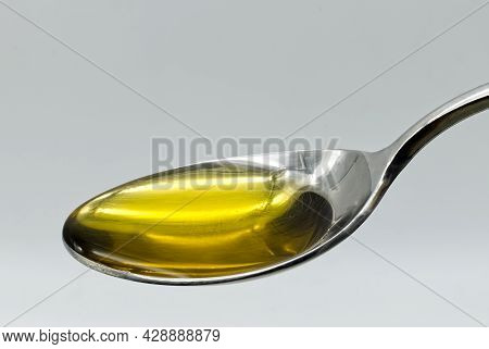 Extra Virgin Olive Oil In A Silver Spoon Isolated On White Background