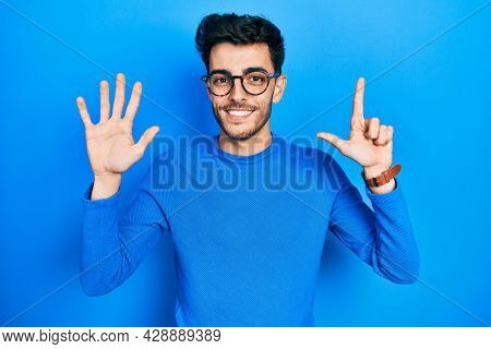 Young hispanic man wearing casual clothes and glasses showing and pointing up with fingers number seven while smiling confident and happy.