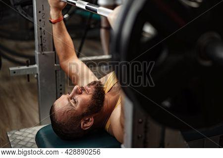 Bearded Man Bodybuilder Doing Bench Press Exercise In Gym