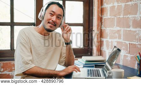 Freelance Asia Guy Headphones Listening Music And Working On Laptop In Living Room At House In The M