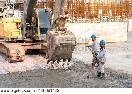 Construction Worker With Excavator Heavy Machine For Concrete Pouring During Commercial Concreting F