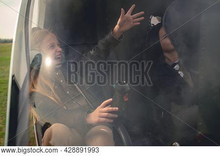 Happy Tween Girl In Aviator Headphones Sitting In Helicopter, Pointing To Sky