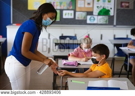 African american female teacher spraying hand sanitizer on hands of boy at elementary school. education back to school health safety during covid19 coronavirus pandemic