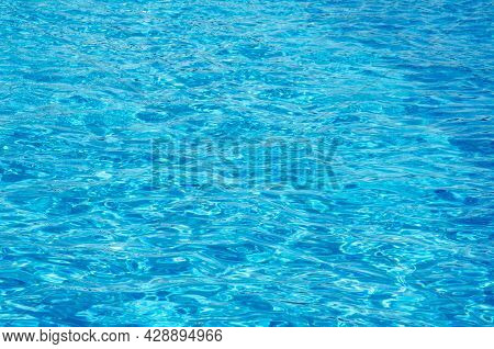 Surface Of Azure Swimming Pool. Top View Rippled Blue Pool Water With Copy Space. Hotel Pool With Su