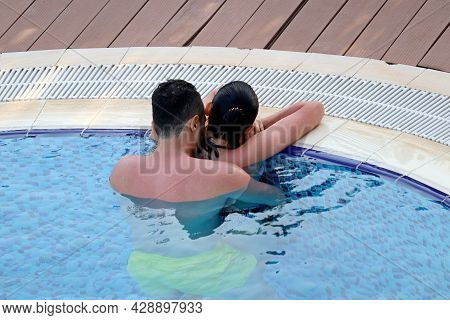 Young Couple Embracing And Kissing In The Pool Water. Passionate Man And Girl At The Poolside, Roman