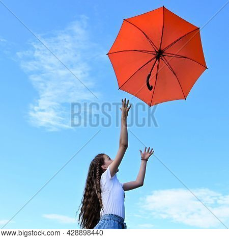 Beautiful Young Girl White T-shirt Throws Up An Orange Umbrella. A Flying Umbrella Against Blue Summ