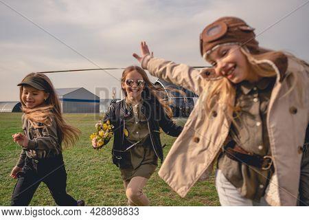Cheerful Tween Girls Running On Flying Field Of Aeroclub