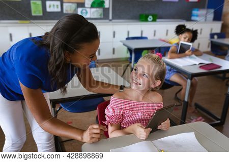 African american female teacher teaching caucasian girl to use digital tablet at elementary school. school and education concept