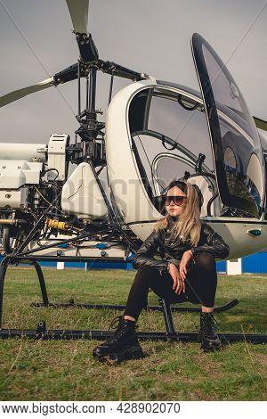 Confident Blonde Tween Girl Sitting On Landing Skids Of Helicopter