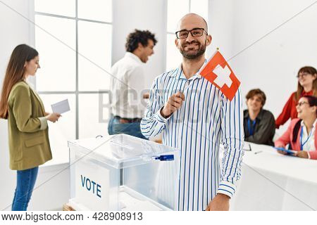 Young swiss voter man smiling happy holding switzerland flag standing by ballot at vote center.