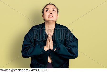 Young hispanic girl wearing sportswear begging and praying with hands together with hope expression on face very emotional and worried. begging.