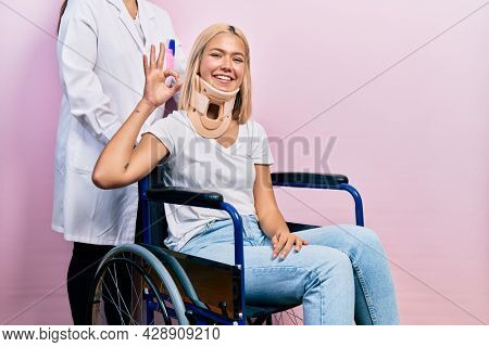 Beautiful blonde woman sitting on wheelchair with collar neck smiling positive doing ok sign with hand and fingers. successful expression.