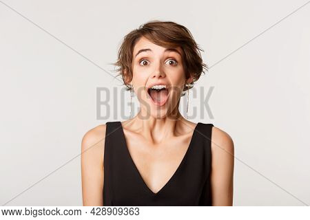 Close-up Of Ecstatic Amazed Girl Drop Jaw And Looking Impressed At Camera, Standing Over White Backg
