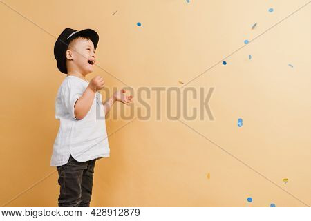 White boy with down syndrome in hat playing with confetti isolated over beige background