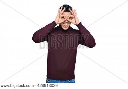 Handsome hispanic man wearing casual turtleneck sweater doing ok gesture like binoculars sticking tongue out, eyes looking through fingers. crazy expression.