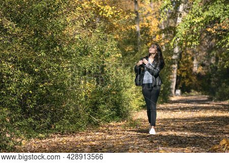 Young Beautiful Woman Walks Along The Alley Of An Autumn Park And Enjoys A Warm Day. Lonely Girl Wal