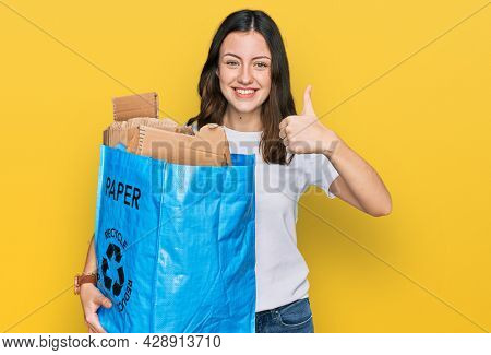 Young beautiful woman holding recycling wastebasket with paper and cardboard smiling happy and positive, thumb up doing excellent and approval sign