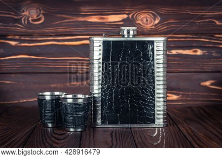 Hip Flask For Whiskey And Two Stainless Steel Lip Tumbler On A Dark Brown Wooden Table. Bar Tools. D