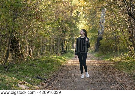Girl Walks In The Autumn Park. Young Beautiful Woman In Black Clothes In The Forest. Alley, Promenad