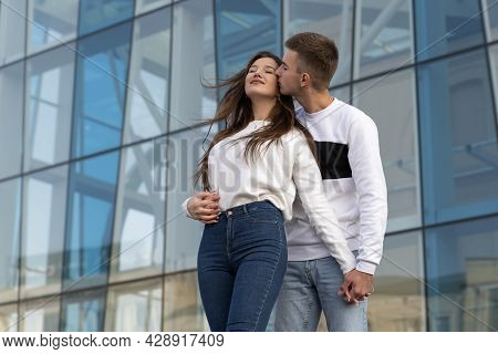 Guy Hugs And Kisses His Girlfriend On The Street. Young Couple In Love. City Building On The Backgro