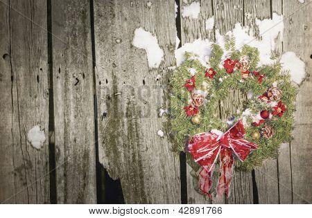 A country Christmas wreath on old barn