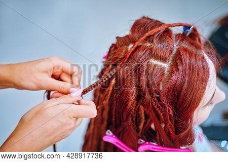 Beauty Salon Services. Girl Hairdresser Weaves Woman Ginger Dreadlocks. Braiding Process Plait With