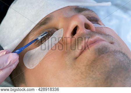 Woman Applies Solution On Mans Eyelashes For Laminating Lifting Lash Procedure.