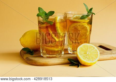 Traditional Iced Tea With Lemon, Mint And Ice In Tall Glasses. Two Glasses With Cool Summer Drink On