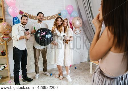 Group of happy friends at a gender reveal baby shower, holding balloon, taking a photo by a photographer