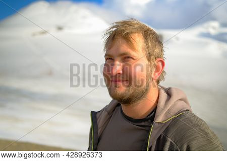 Portrait Of A Happy Unshaven Man In The Mountains. Tourist Climber On The Background Of Mountains. C