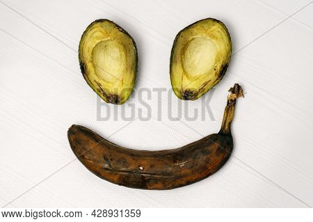 Overripe Fruits On White Background In Shape Of Antropomorphic Smiling Face. Dirty Spots, Tainted Ba