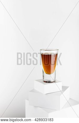 Old Golden Cognac In Shot Glass On Top Of Stack Of White Square Podiums, Luxury Alcohol Drink In Mod