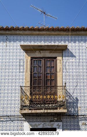 Travel To Portugal. Old Vintage Facade And Balcony Door From House Exterior In Portuguese Typical Tr
