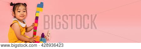 Pleased Asian Toddler Girl In Yellow Dress Playing Colorful Building Blocks Isolated On Pink, Banner