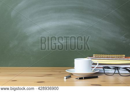 Stacked Notebooks And Cup Of Coffee On Wooden School Desk With A Green Chalkboard. The Blank Blackbo