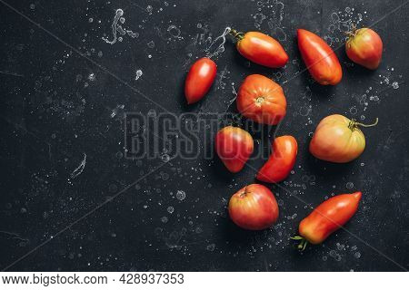 Ripe Fresh Tomatoes Elongated And Heart Shapes On Black Stone Background. Top View, Flat Lay, Copy S