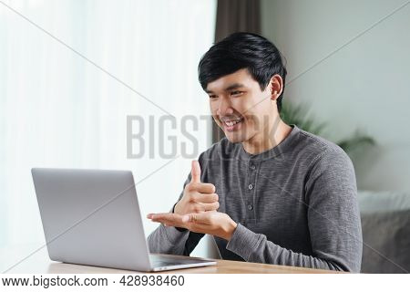 Young Asian Man Deaf Disabled Using Laptop Computer For Online Video Conference Call Learning And Co