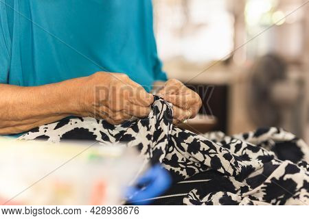 Elderly Woman Hands Using Needle And Thread To Mend A Dress.