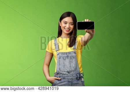 Attractive Cheerful Asian Brunette Female Introduce Smartphone Game, Hold Telephone Horizontal, Show