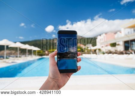 Young Woman Makes Photo Of Swimming Pool Area, Blue Sky And Beautiful Landscape At Background On Sma