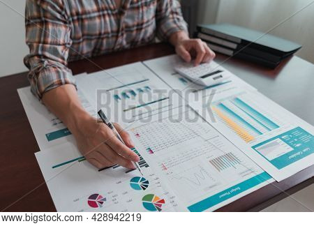 Businessman Calculates And Analysis Chart Statistics About Tax, Accounting, Math Finance, On Wooden