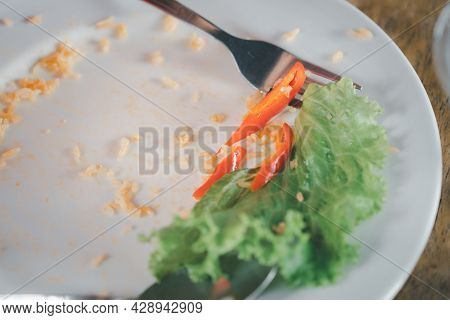 Scrap Of Chili With Lettuce On Dish After Eating. The Leftover Food On The Restaurant Table