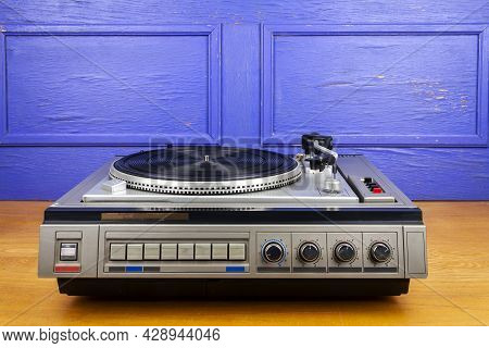 Vintage Turntable Vinyl Record Player On Table By Blue Wall.