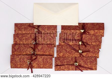 Wedding Invitations With Gold Wedding Decorative Rings And Envelope On A White Background
