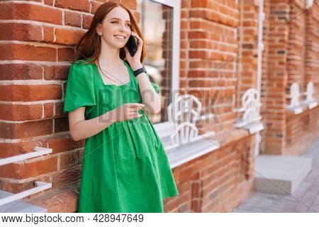 Portrait Of Young Smiling Woman Talking On Mobile Phone Standing Leaning On Old Red Stone Wall Of Bu
