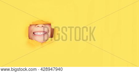 Breaking Paper Background. Emotions Concept. Kid With Toothy Smile Shows Face In Paper Hole