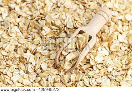 Wooden Scoop Of Dry Raw Rolled Oat Flakes Top View